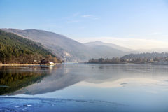 De wintermeer met bergen stock foto