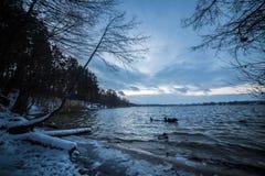 De wintermeer na zonsondergangijswater Stock Foto