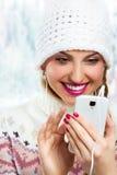 De wintermeisje het luisteren muziek die telefoon met hoofdtelefoons met behulp van Stock Afbeeldingen