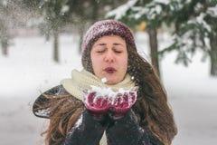 De wintermeisje met een rode hoeden blazende sneeuw stock afbeelding