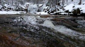 De wintermening over schuimende snelle stroom in cascade van waterval Bezinningen van bewolkte hemel in waterspiegel Diepvries stock videobeelden