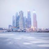 De wintermening van het commerciële centrum onder de sneeuwval en de mist stock fotografie