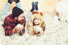 De winterpartij en vooravond De vader en de dochter liggen in veren, Kerstmis Mens hipster en kindglimlach bij Kerstmis Familie royalty-vrije stock fotografie