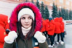 De winterportret van een jonge vrouw tegen de achtergrond van mensen in rode jasjes royalty-vrije stock afbeeldingen