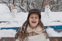 De winterportret van een mooi meisje met gebreide hoed in de sneeuw Stock Afbeeldingen