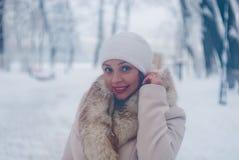De winterportret van een vrouw in witte laag en hoed tijdens sneeuwval in een park Stock Foto's
