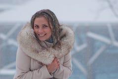 De winterportret van een vrouw in witte laag tijdens sneeuwval in een park Stock Afbeelding