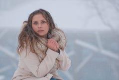 De winterportret van een vrouw in witte laag tijdens sneeuwval in een park Stock Foto's