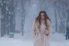 De winterportret van een vrouw in witte laag tijdens sneeuwval in een park Royalty-vrije Stock Afbeelding