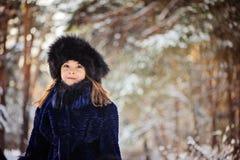 De winterportret van glimlachend kindmeisje in bonthoed en laag Stock Afbeeldingen