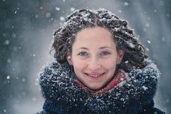 De winterportret van het schoonheidsmeisje met vliegende sneeuwvlokken Stock Afbeeldingen