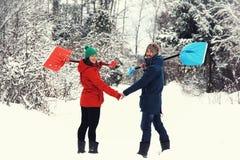 De winterpret: gelukkig paar met sneeuwschoppen Stock Afbeelding
