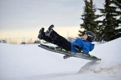 De winterpret - Kind Sledding/Tobogganing snel over Sneeuwhelling Stock Foto