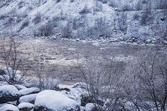 De winterrivier die door de rotsen vloeien Stock Foto