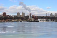 De winterrivier met ijs op de achtergrond van het stedelijke landschap wordt behandeld dat Stock Foto