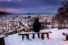 De winterscène met Eenzame Mensenzitting op Sneeuwbank die naar Stadscentrum kijken bij Schemering stock fotografie
