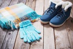 De winterschoenen, handschoenen, sjaals op houten achtergrond Royalty-vrije Stock Fotografie