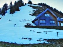 De wintersfeer op weilanden en landbouwbedrijven in de Urnasch-gemeente stock fotografie