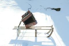 De winterslee op sneeuw en harmonika royalty-vrije stock afbeelding