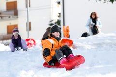 De wintervakantie die met loodje op de sneeuw in de winter spelen stock afbeeldingen