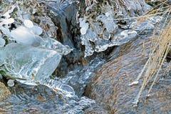 De wintervallei van de bevroren die stroom van de bergrivier met ijs en sneeuw bij kleurrijke zonsondergang lichte dageraad wordt Stock Afbeeldingen