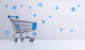 De winterverkoop: Boodschappenwagentje en sneeuwvlokken royalty-vrije stock afbeeldingen