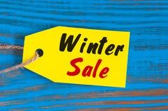 De winterverkoop, prijskaartje op blauwe houten achtergrond Stock Fotografie