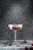 De winterviering - glas van koude cocktaildrank met rode vruchten in sneeuw royalty-vrije stock foto's
