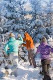 De wintervrienden die van de sneeuwbalstrijd pret hebben Royalty-vrije Stock Foto