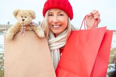 De wintervrouw die kleinhandels het winkelen of giftzakken houden stock afbeeldingen