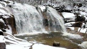 De winterwaterval Kleine vijver en de sneeuwcascade van de keienblaasbalg van waterval Het water van de kristalvorst van bergrivi stock videobeelden