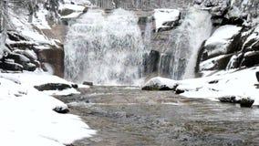 De winterwaterval Kleine vijver en de sneeuwcascade van de keienblaasbalg van waterval Het water van de kristalvorst van bergrivi stock video
