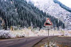 De winterweg in de bergen en verkeersteken Stock Foto