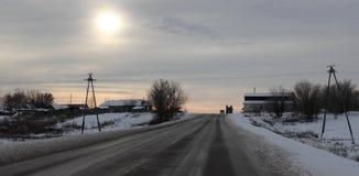 De winterweg die door het platteland overgaan royalty-vrije stock afbeeldingen