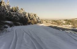 De winterweg en bergen stock fotografie