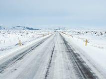 De winterweg met berg aan de kant van de weg met s wordt behandeld dat Royalty-vrije Stock Afbeeldingen