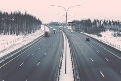 De winterweg met vrachtwagens en auto's onder gestemde de winter bos Uitstekende stijl royalty-vrije stock foto's