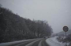 De winterweg onder het sneeuwen Stock Foto