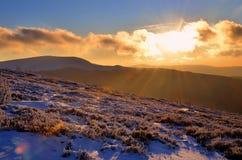 De winterzonsondergang in bergen Stock Foto's