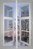 De winterzonsondergang die door oud venster wordt bekeken stock foto