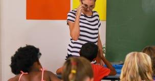 De wiskunde van het leraarsonderwijs aan schooljonge geitjes in klaslokaal stock videobeelden