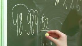 De wiskundeles bij schoolkinderen lost problemen bij het bord en bij hun bureaus op stock videobeelden