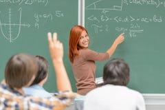 De wiskundestudent schrijft op groene bordklasgenoten stock fotografie