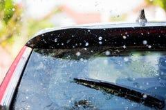 De wisser op achterruit van een auto met dalingsregen stock afbeelding