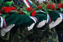 De wit-gloved handen houden een kroon en bloemen in geheugen van die gedood in oorlogen en gewapende conflicten stock afbeelding