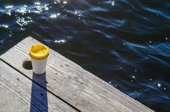 De Witboekkop met een geel plastic deksel bevindt zich op de raad op de kust van het meer stock afbeeldingen