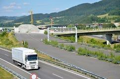 De witte aandrijving van de MENSENvrachtwagen op Slowaakse D1 weg Op achtergrond is nieuw deel in aanbouw van deze manier Stock Foto's