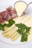 De witte asperge met ham en hollandaise saus stock foto