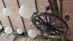 De witte ballen en een houten wiel met kaars-lampen hangen op het plafond stock videobeelden