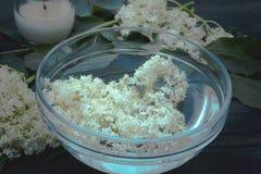 De witte bloemen en de bladeren van vlierbes liggen op een kom op een rustieke houten achtergrond stock foto